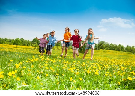 Group of happy kids running in the yellow flowers field summer day - stock photo