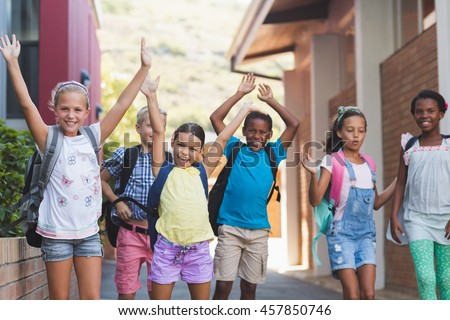 Group of happy kids standing in a row with hands raised at school campus - stock photo