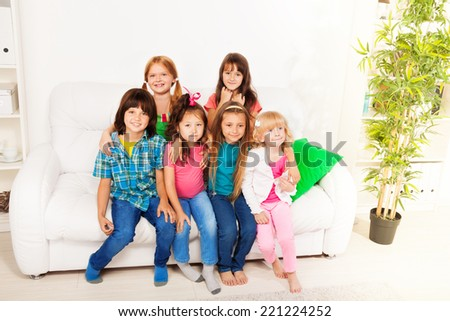 Group of 6 happy little kids sitting together on the couch at home interior in living room smiling and having fun a