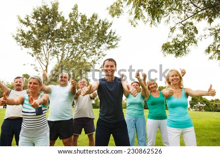 Group of happy men and women showing thumbs up - stock photo