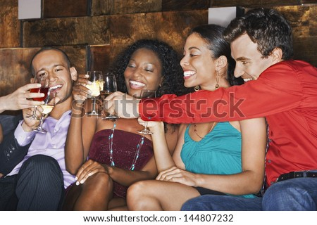 Group of happy multiethnic friends toasting drinks in bar - stock photo