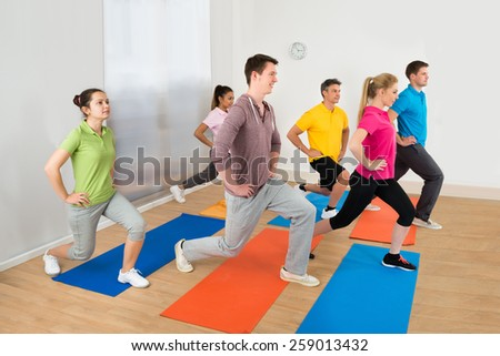 Group Of Happy Multiethnic People Doing Exercise In Gym - stock photo