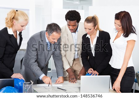 Group Of Happy Multiracial Businesspeople Discussing Together In Office - stock photo