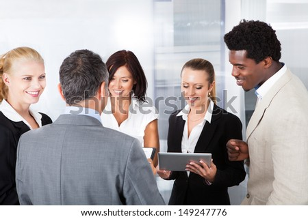 Group Of Happy Multiracial Businesspeople Looking At Digital Tablet - stock photo