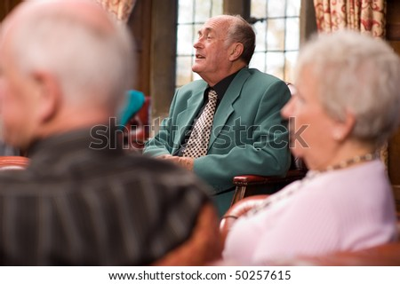 Group of happy older senior friends enjoying each others company in an expensive hotel - stock photo