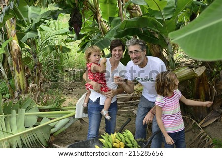 Group of happy people, farmer and customer family, in banana plantation - stock photo