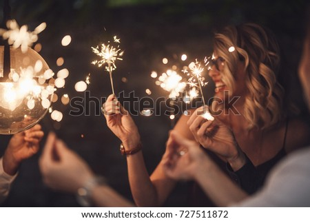 Group of happy people holding sparklers at party and smiling.