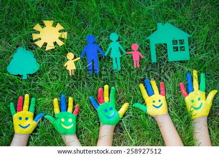 Group of happy people on green grass. Family having fun in spring. Smiley on hands. Ecology concept. Top view portrait - stock photo