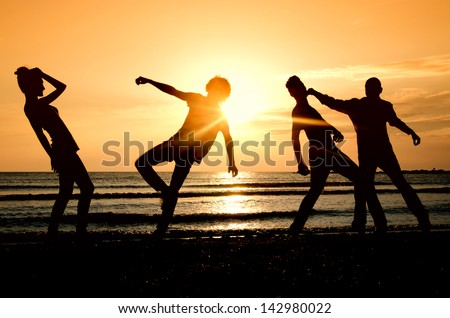 Group of happy people parting on the beach at sunrise, people fighting and getting fit in the morning