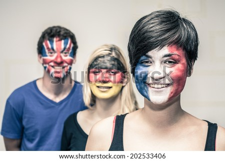 Group of happy people with painted flags on their faces. - stock photo