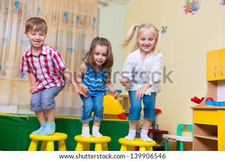 Group of happy preschool kids jumping in kindergarten - stock photo