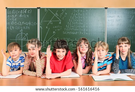 Group of happy school children at a classroom raising their hands. Education. - stock photo