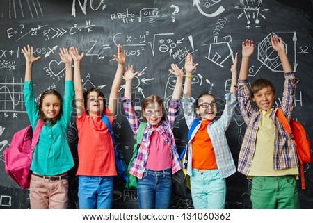Group of happy schoolchildren standing in front of the blackboard with hands up - stock photo