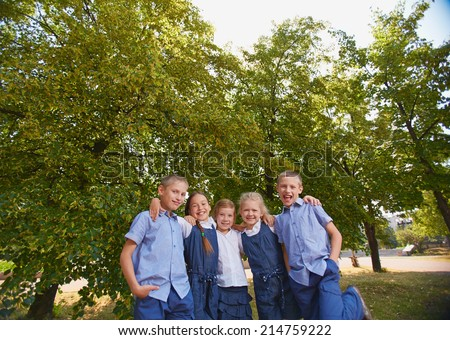 Group of happy schoolkids looking at camera in park - stock photo