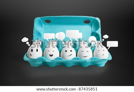 Group of happy smiling eggs with social chat sign and speech bubbles.  Ten white eggs in a carton box representing a social network. On a black background - stock photo