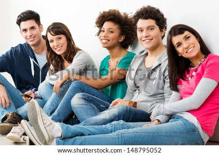 Group Of Happy Smiling Friends Sitting In A Row indoor  - stock photo