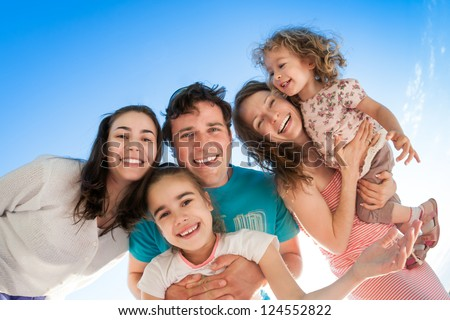 Group of happy smiling people against blue sky - stock photo