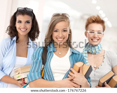 Group of happy student girls on school corridor looking at camera, smiling. - stock photo