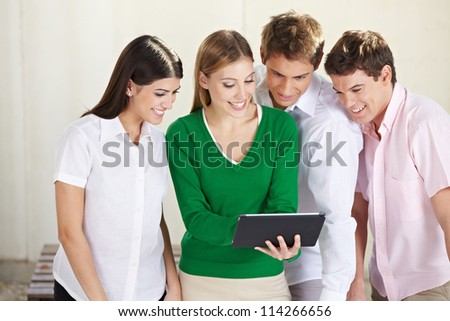 Group of happy students looking at a tablet computer - stock photo
