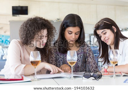 Group of happy students preparing their exams or simply relaxing at a bar