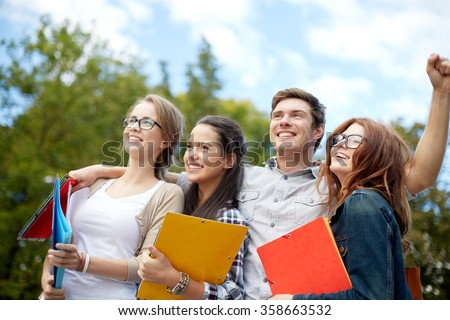 group of happy students showing triumph gesture - stock photo