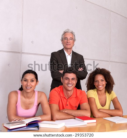 Group of happy students studying with lecturer - stock photo