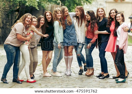 Group of happy stylish women having fun on background of old european city street, travel or celebrating friendship concept, moments of happiness