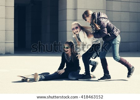 Group of happy teen girls with skateboard on city street - stock photo