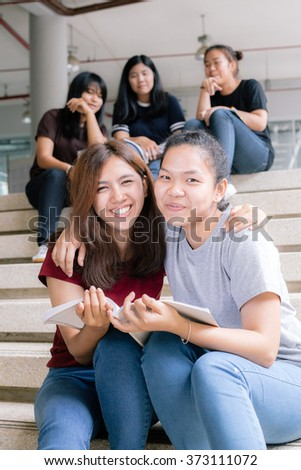 group of happy teen high school students outdoors, Asian, tutoring  - stock photo