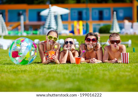 group of happy teenage friends lying on summer lawn - stock photo