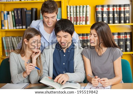 Group of happy university students studying together in library - stock photo
