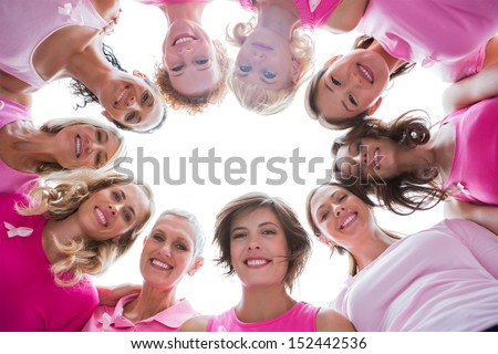 Group of happy women in circle wearing pink for breast cancer on white background - stock photo