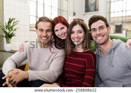 Group of Happy Young Adult Closed Friends Sitting on the Couch While Looking at Camera with happy Facial Expressions. - stock photo