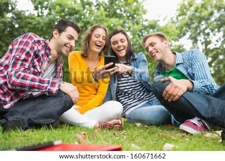Group of happy young college students looking at mobile phone in the park - stock photo