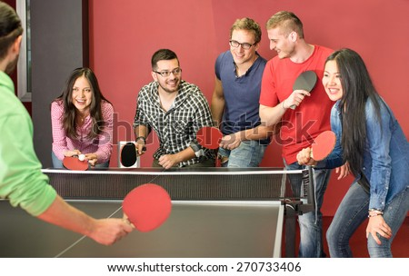 Group of happy young friends playing ping pong table tennis - Fun moment in game room of traveler youth hostel - Concept of vintage sport and genuine emotions - Main focus on two guys with eye glasses - stock photo