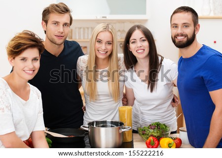 Group of happy young friends preparing lunch standing smiling at the camera grouped around the stainless steel pot and fresh healthy ingredients - stock photo