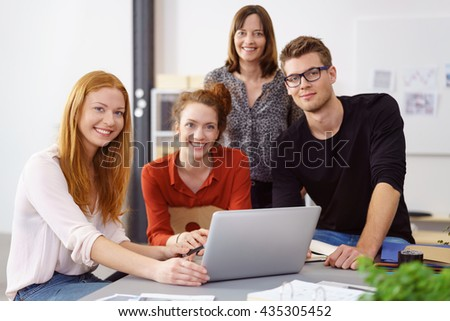 Group of happy young office co-workers working as a business team sitting grouped around a laptop computer smiling at the camera - stock photo