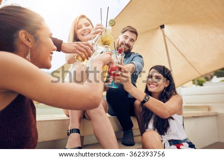 Group of happy young people cheering with cocktails and smiling while partying together on rooftop. Multiracial young friends hanging out. - stock photo