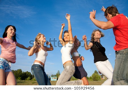 group of happy young people dancing on the beach at  summertime - stock photo