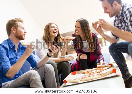 Group of happy young people eating pizza in the room - stock photo