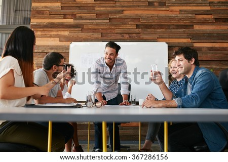 Group of happy young people having a business meeting. Creative people sitting at table in boardroom with man explaining business strategy. - stock photo
