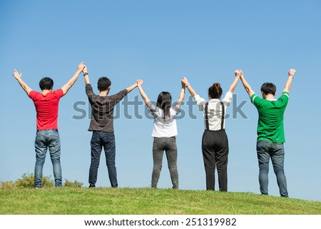 group of happy young people holding hands raised together in park of Bangkok Thailand - stock photo