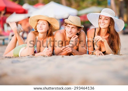 Group of happy young people in bathing suits enjoying sunset on the beach and having fun during joyful holidays - stock photo