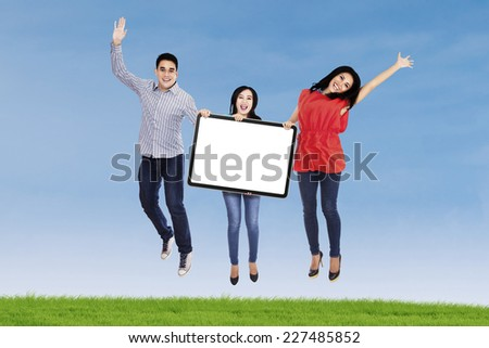 Group of happy young people jumping together and holding a blank board - stock photo