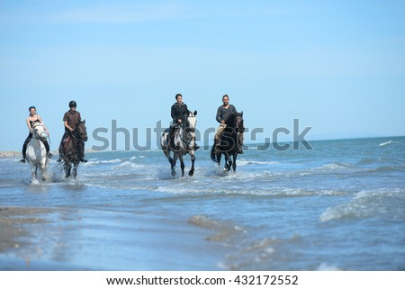 group of happy young people on vacation riding horses on the beach in a sunny summer day - stock photo