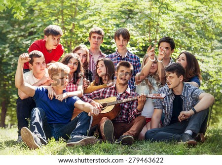Group of happy young people singing with guitar together - stock photo