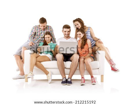Group of happy young people sitting on sofa and using digital tablet and laptop, isolated on white background. Best friends - stock photo