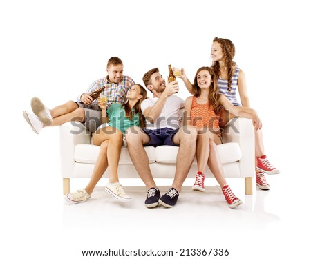 Group of happy young people sitting on sofa with bottled drinks, isolated on white background. Best friends - stock photo