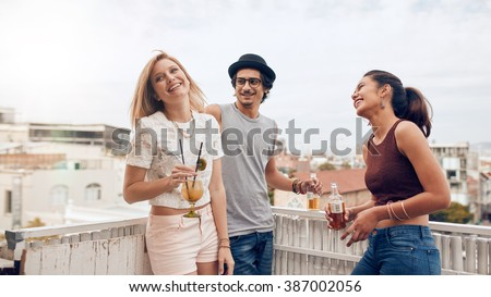 Group of happy young people standing together with drinks. Mixed race friends having rooftop party. - stock photo