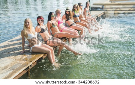 group of happy young woman feet splash water in sea and spraying at the beach on beautiful summer sunset light. Eight sexy girls playing on wooden pontoon against blue sky background Enjoy holiday - stock photo
